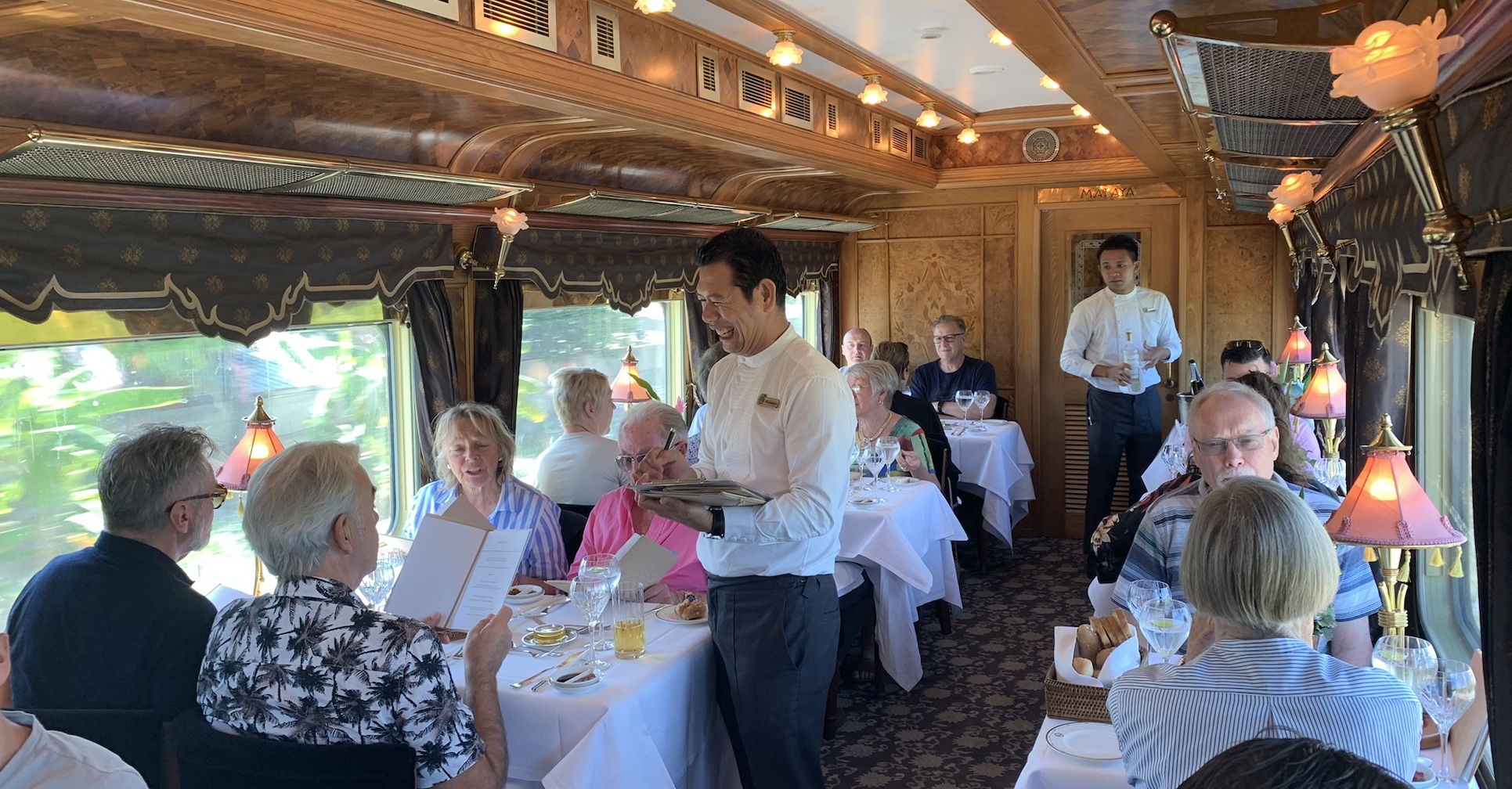 Server with guests in dining car on Eastern & Oriental Express