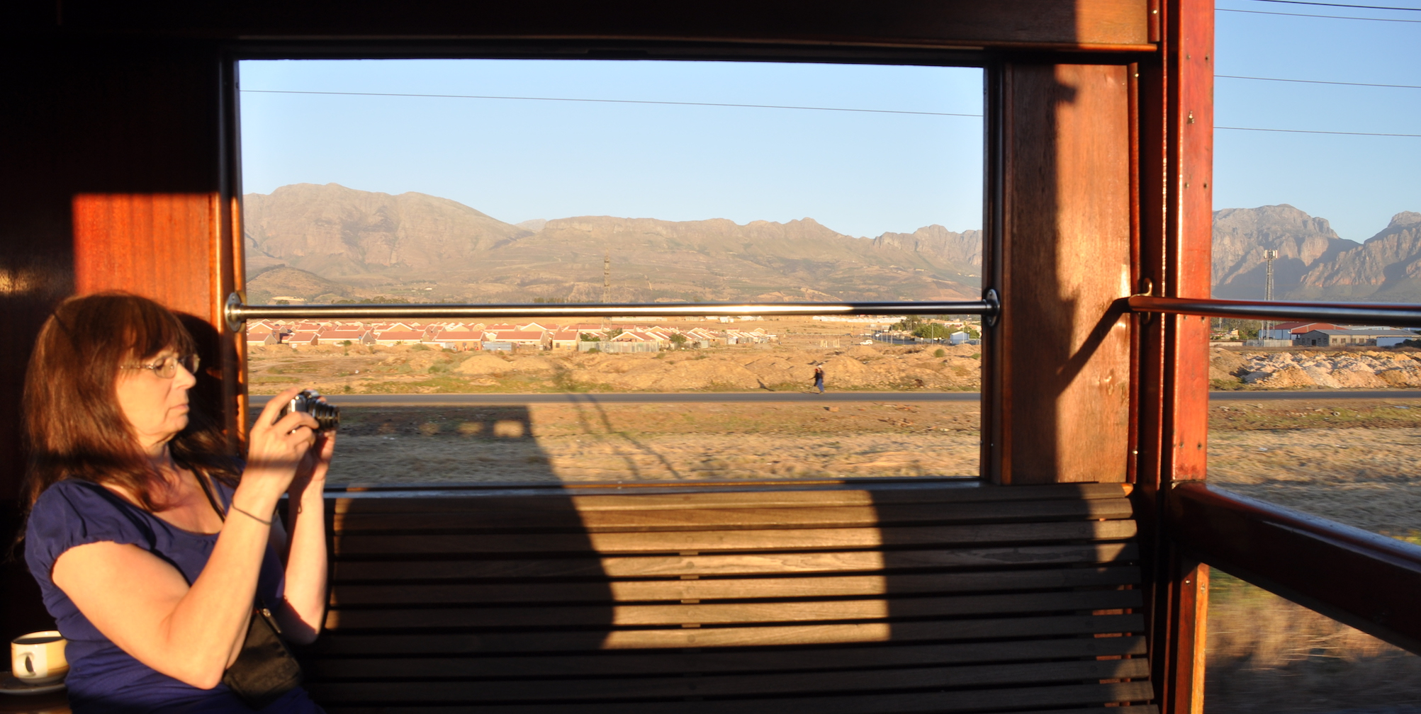 Woman takes photo from Rovos Rail observation platform.