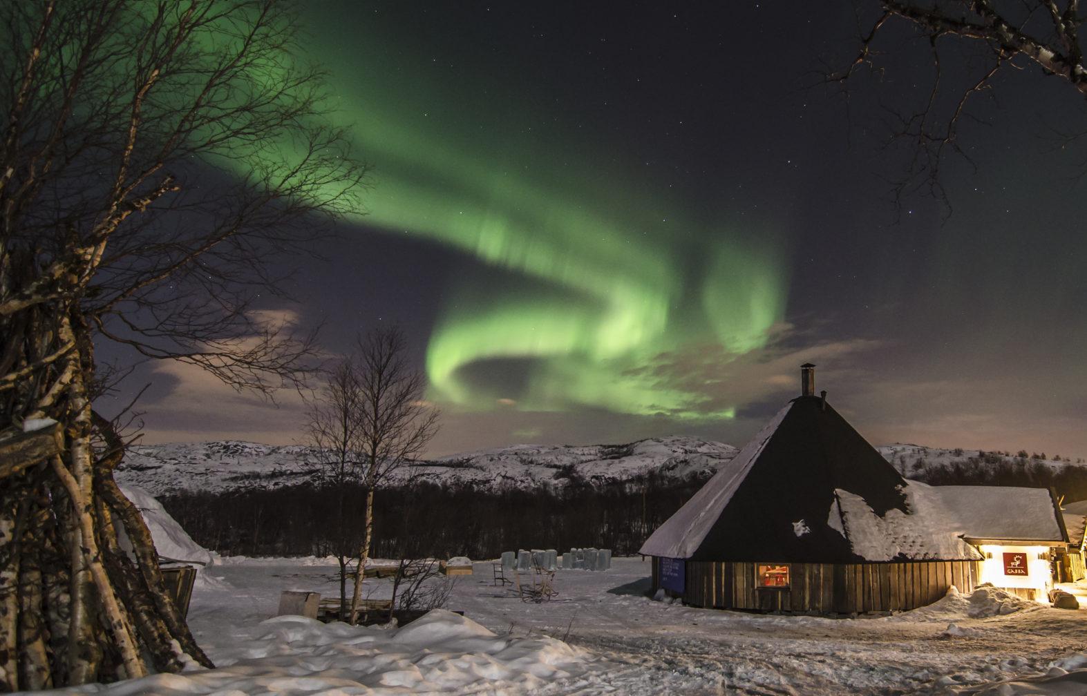 King Crab log cabin with Northern Lights overhead in Kirkenes, Norway.