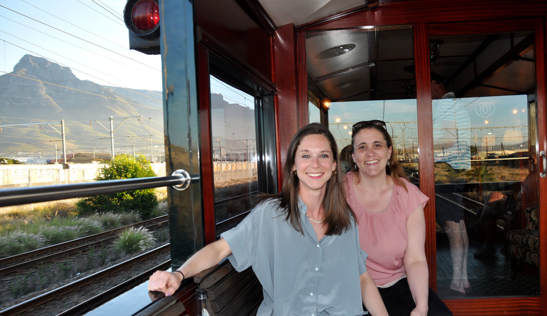 IRT's Angela Walker & Rachel Hardy enjoy the breeze on the observation car as the Pride of Africa arrives in Cape Town. IRT Photo.