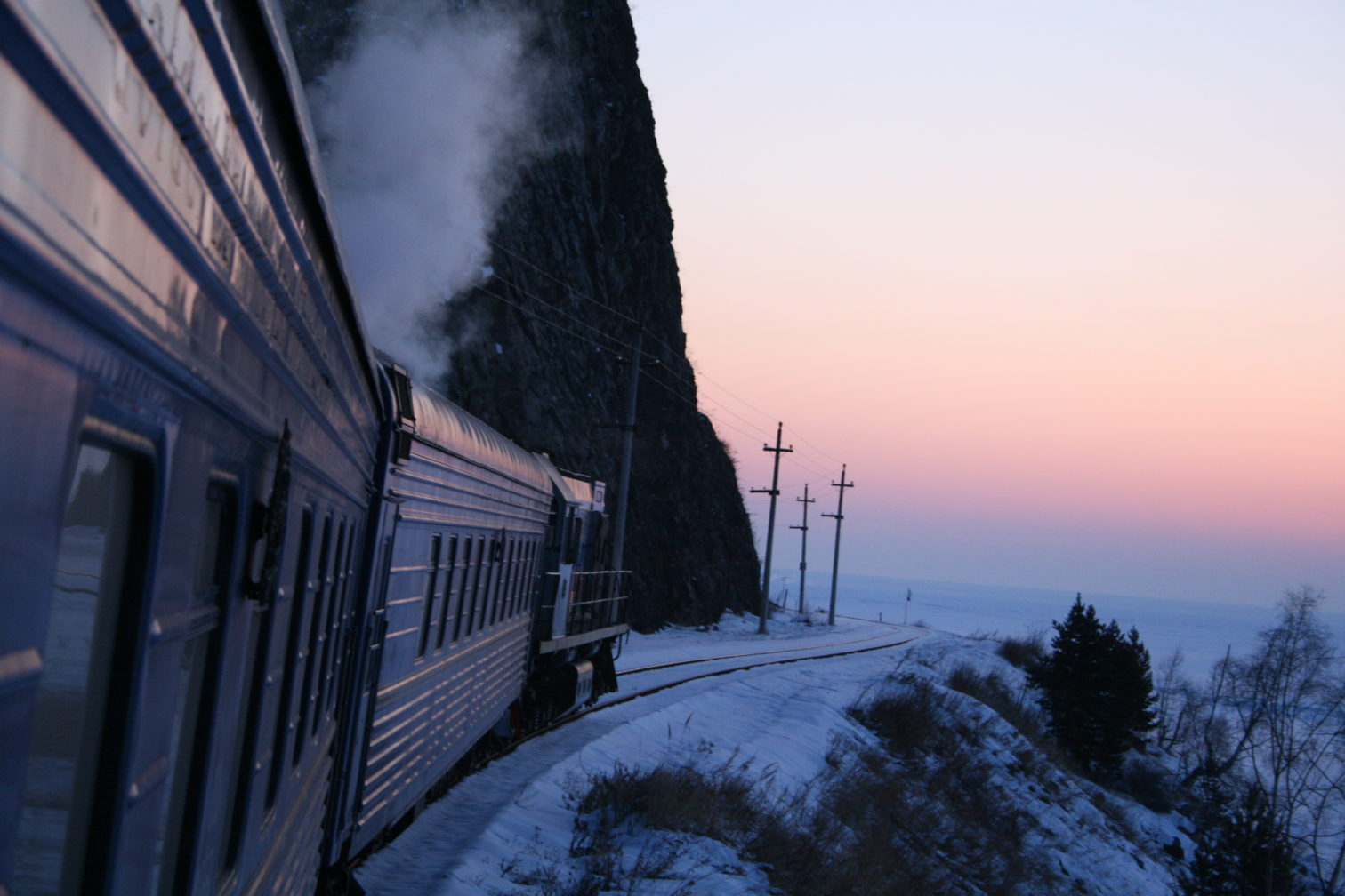 A blue train steams through a wintry scene in Russia.