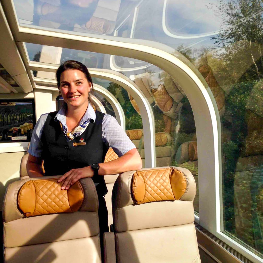 Stewardess standing by seats on the Canadian Rockies Getaway Circle journey