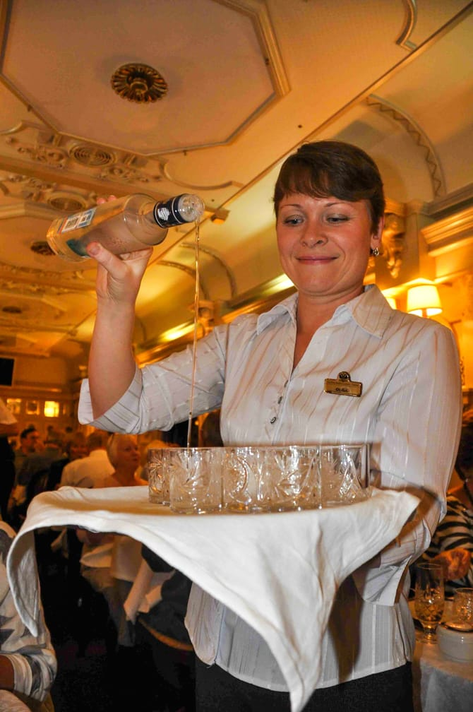 Woman serving vodka on the A Caspian Odyssey Along the Ancient Silk Road journey