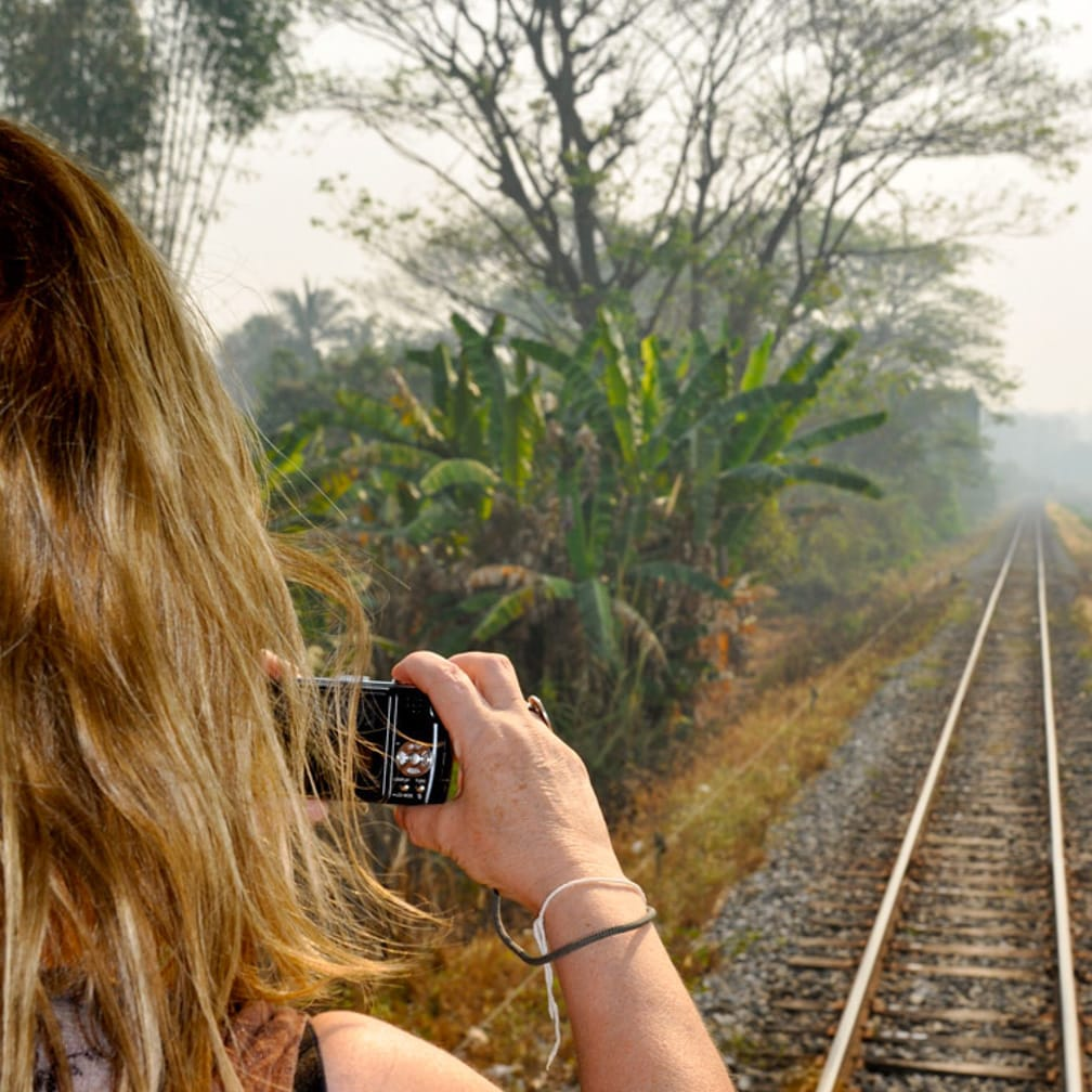 Woman taking photos from the rear lounge on the Kuala Lumpur-Bangkok by Luxury Train journey