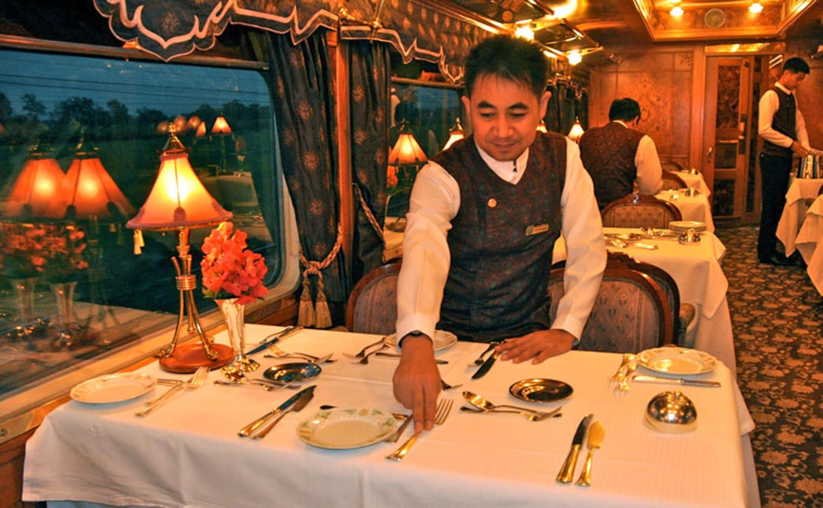 Waiter setting a table on the Kuala Lumpur-Bangkok by Luxury Train journey