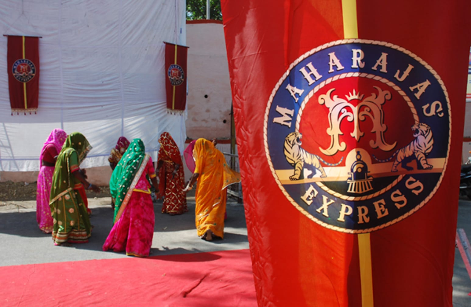Flag with women in the background on the Maharajas' Express Indian Splendor, Delhi-Mumbai journey