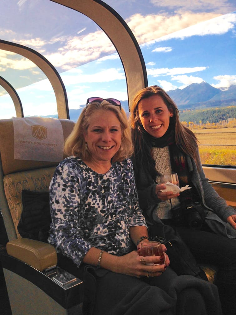 Two female guests riding in a train on the Rocky Mountaineer: Journey through the Clouds Explorer journey