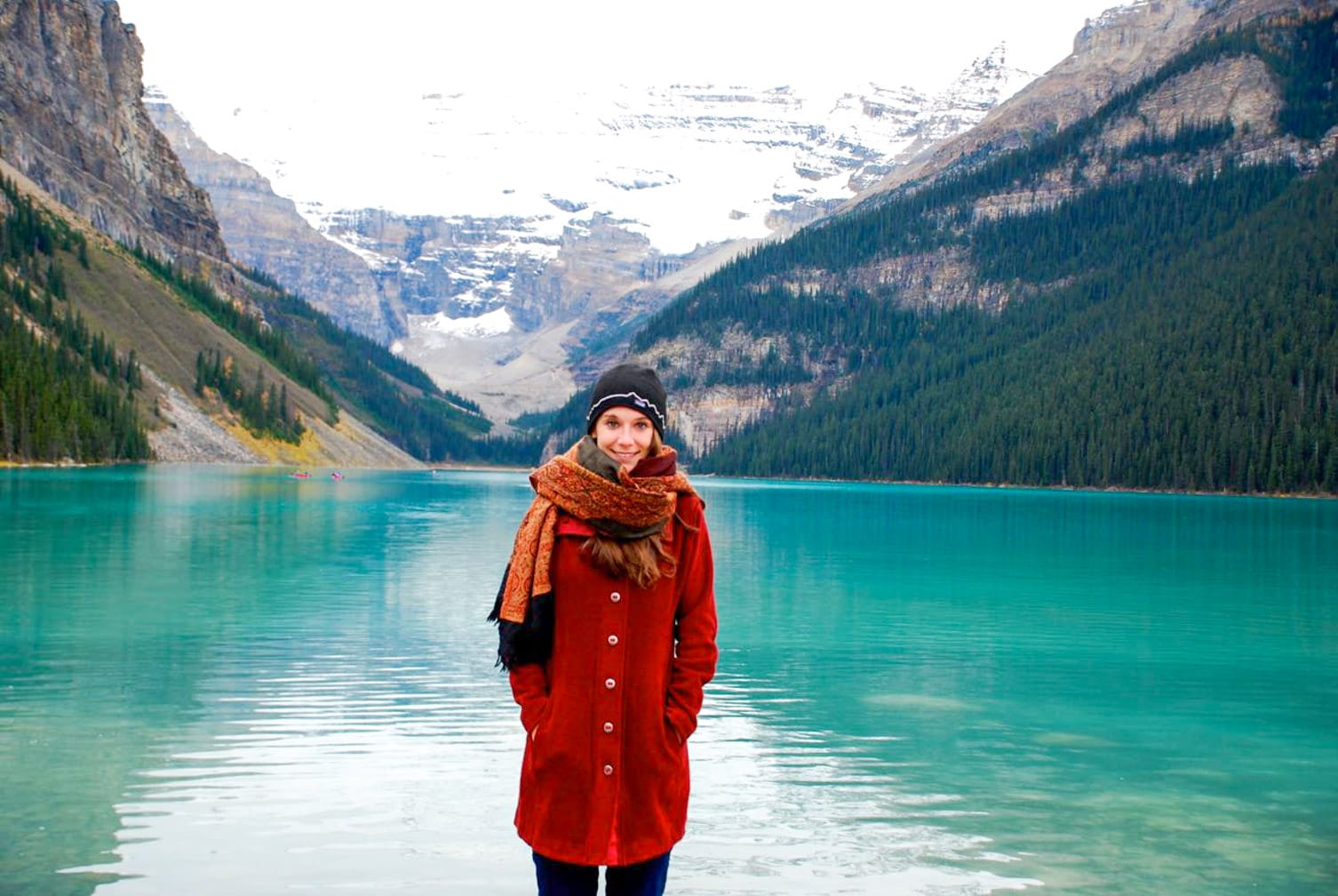 Woman standing by a glacier lake on the Rocky Mountaineer: Journey through the Clouds Explorer journey