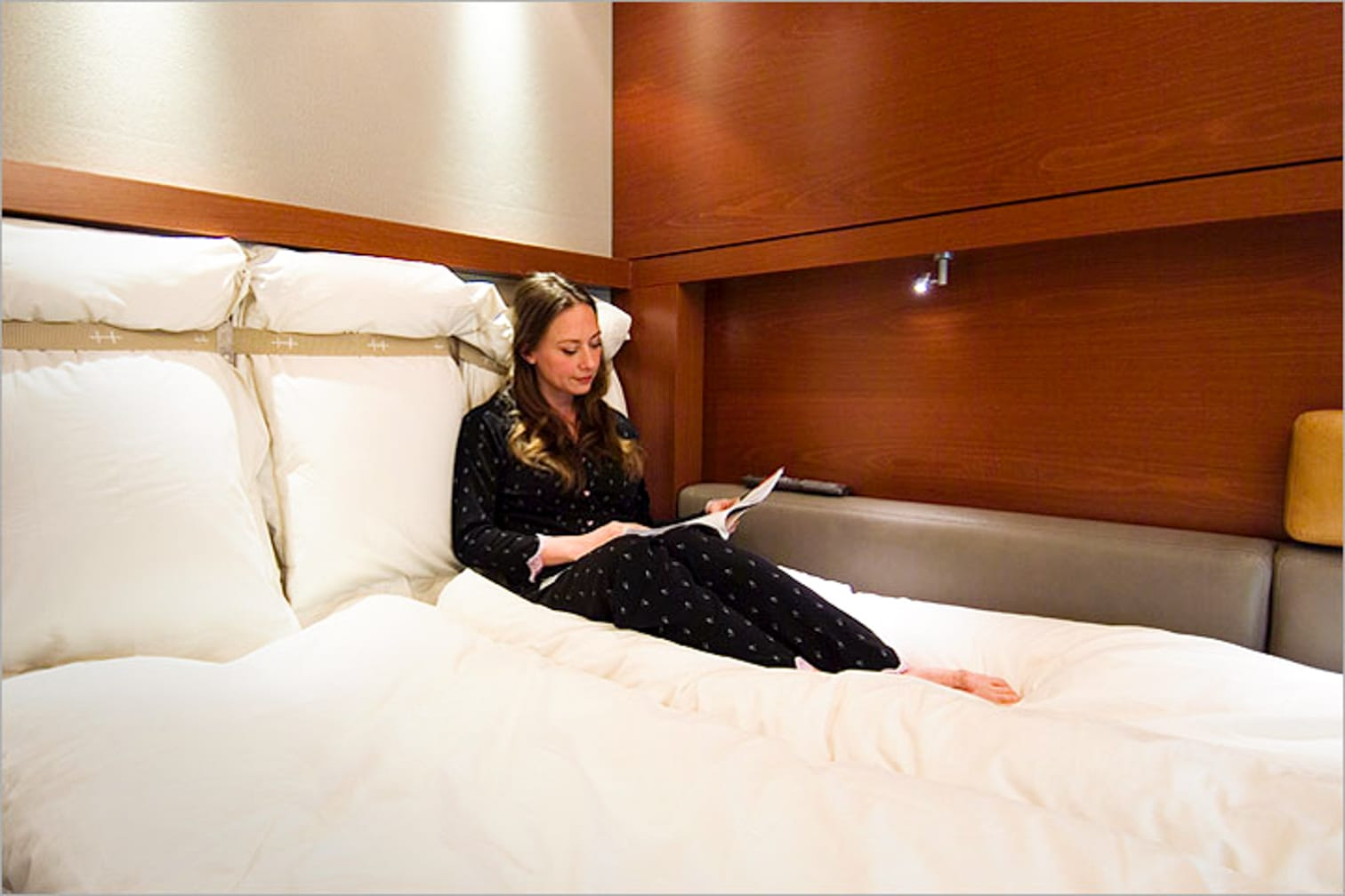 Woman reading in bed on the Trans-Canada Rail Adventure: Vancouver-Toronto journey