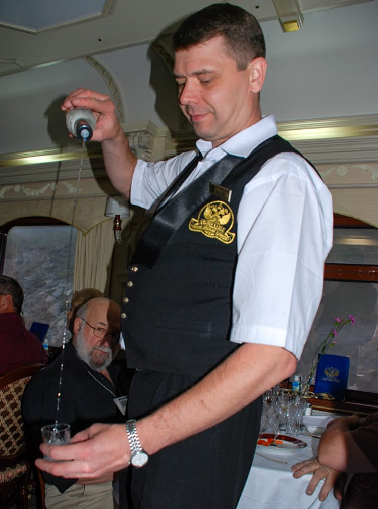Server pouring vodka on the Ulaan Baatar Express: Moscow to Ulaan Baatar journey