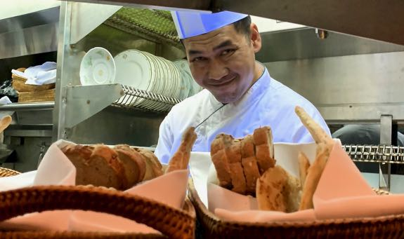 Chef smiling behind bread