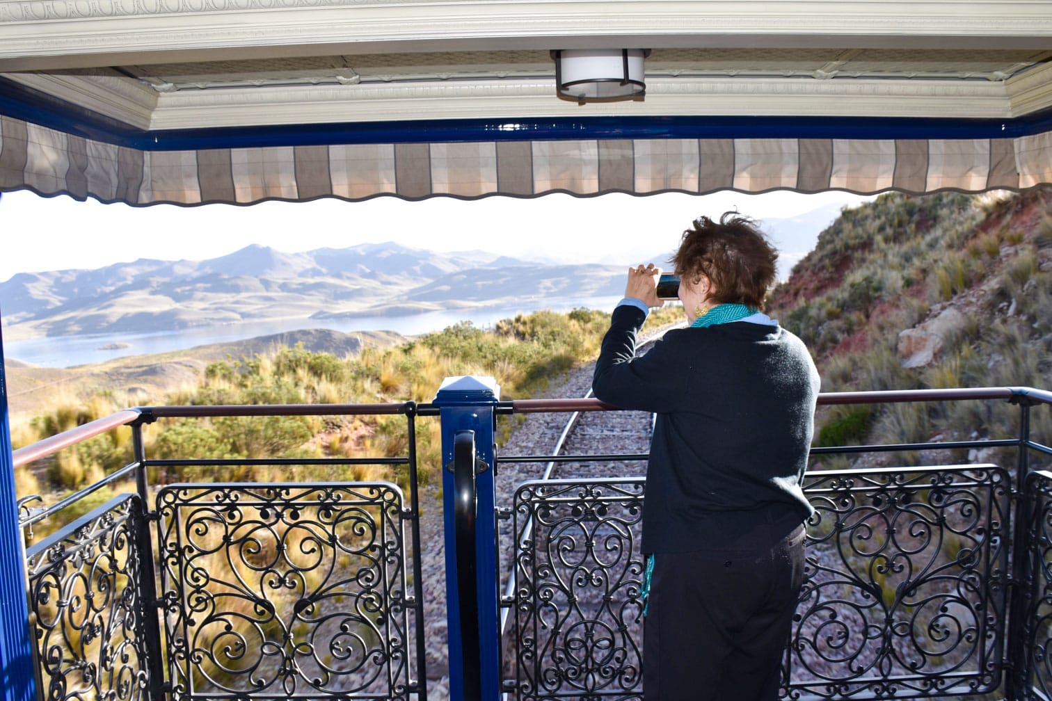 Woman using binoculars on the Belmond Andean Explorer train