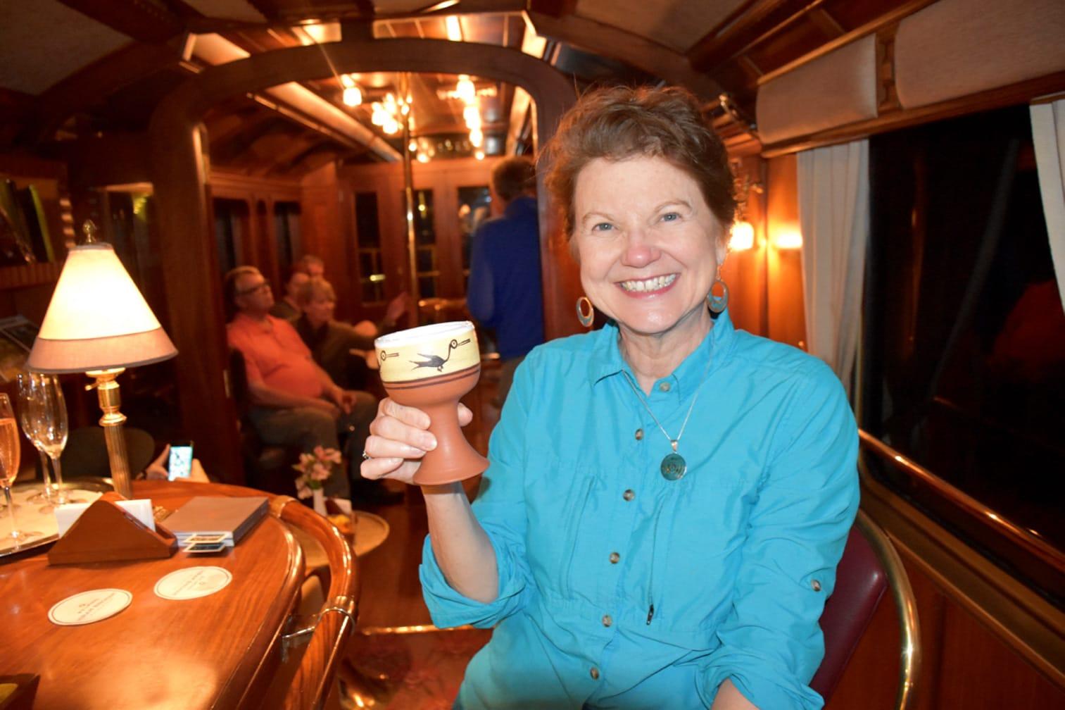 Female guest holding a drink on the Belmond Hiram Bingham train