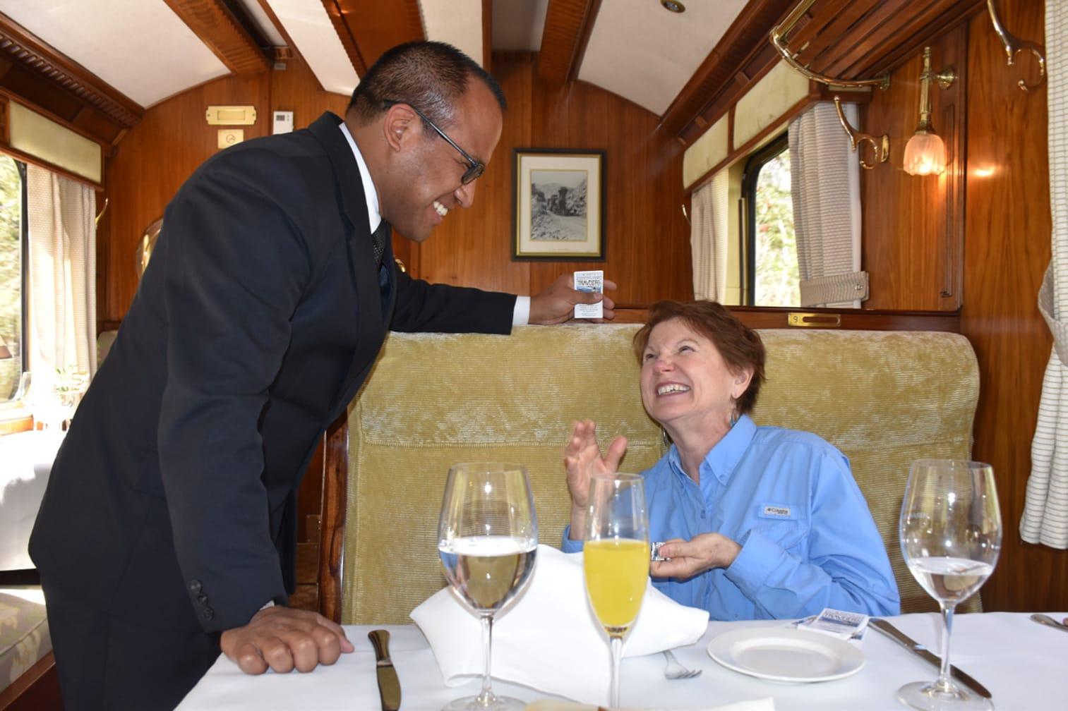 Belmond Hiram Bingham train staff speaking with a guest