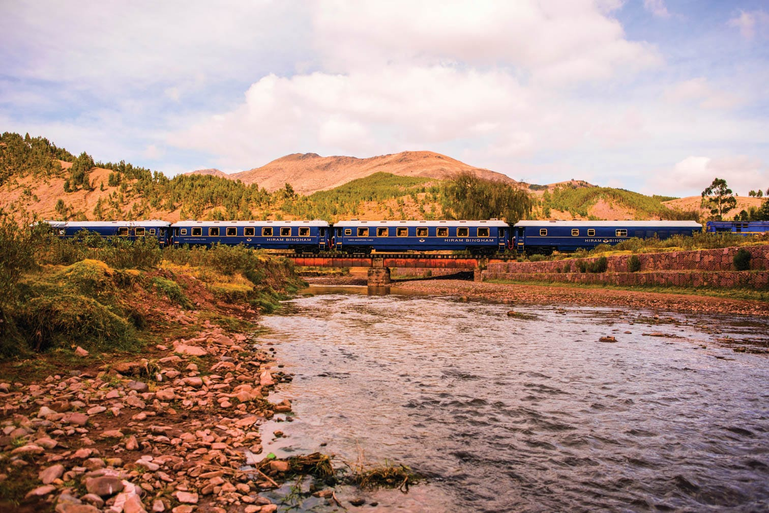 Belmond Hiram Bingham train traveling past water and mountains