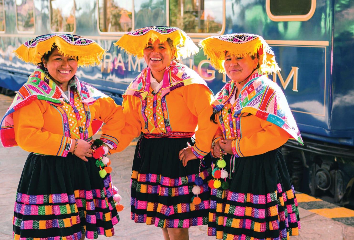 Three women in traditional costume on the Belmond Hiram Bingham train
