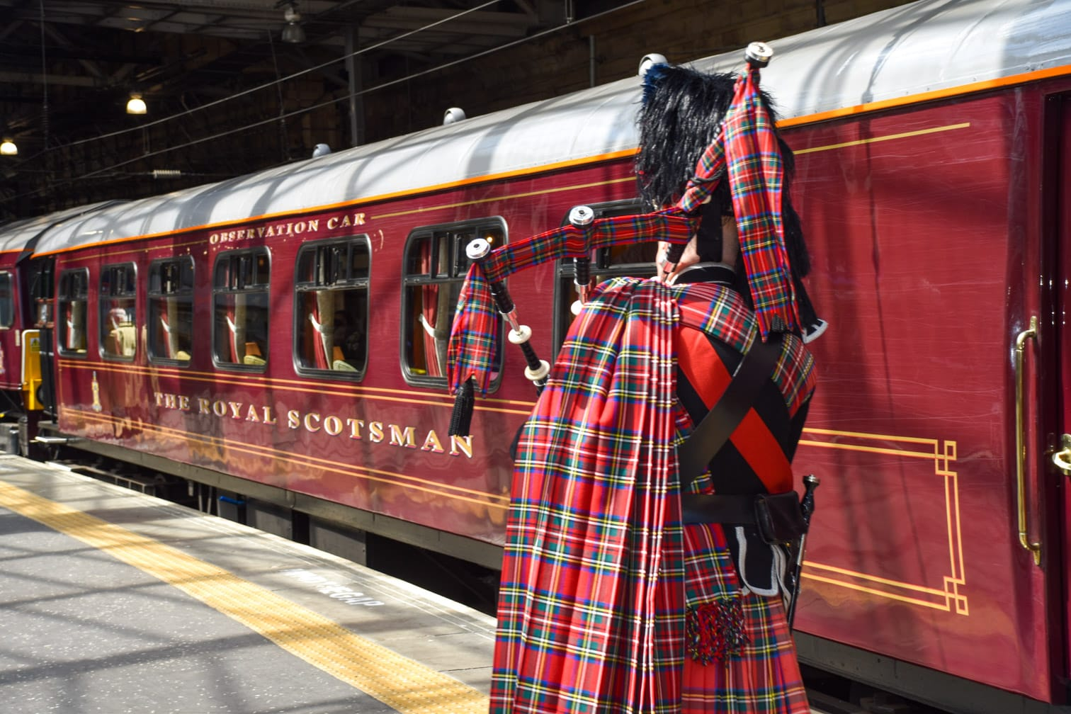 Scottish man playing bagpipes by the Belmond Royal Scotsman train
