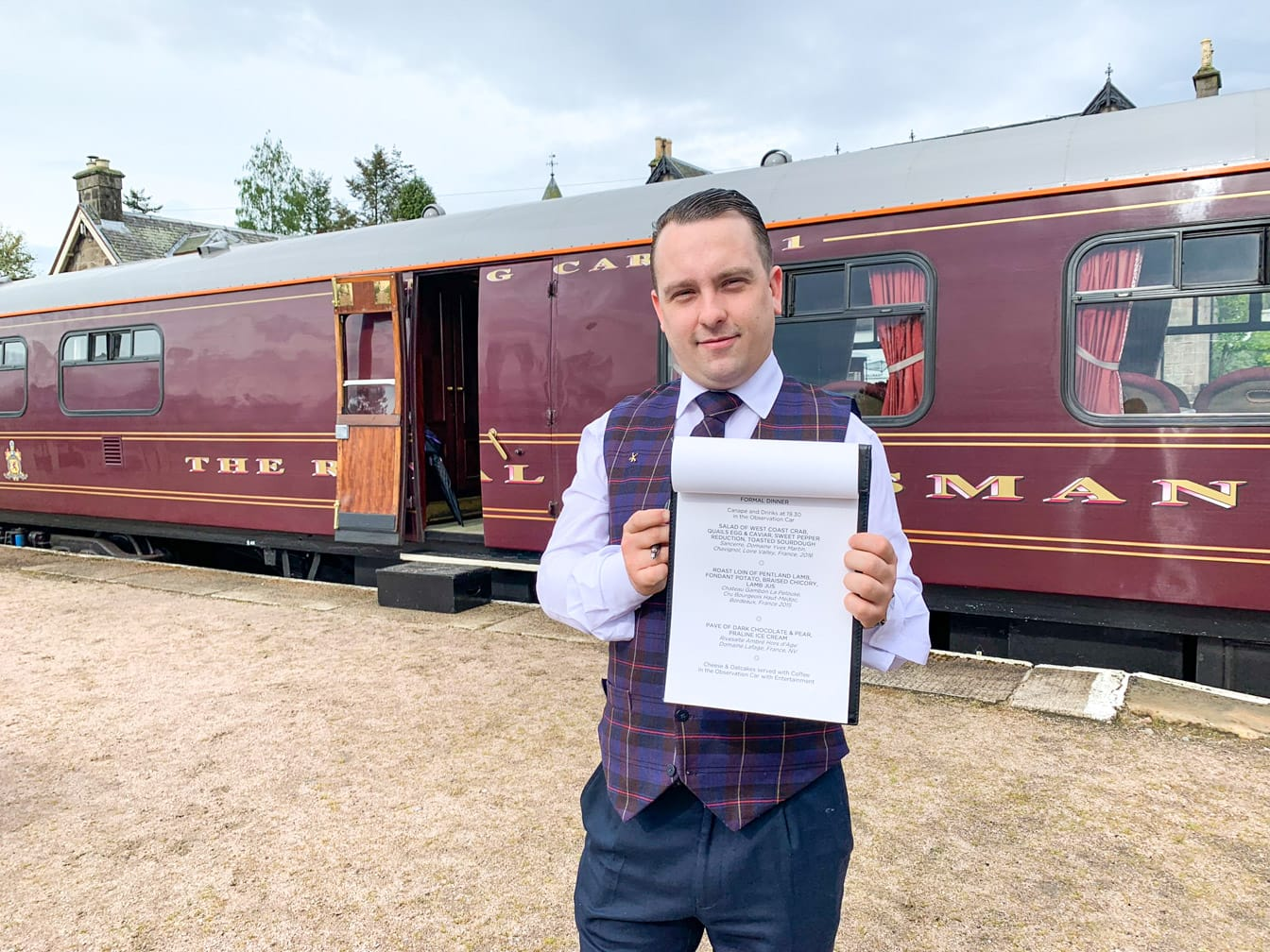 staff holding a sign on the Belmond Royal Scotsman train