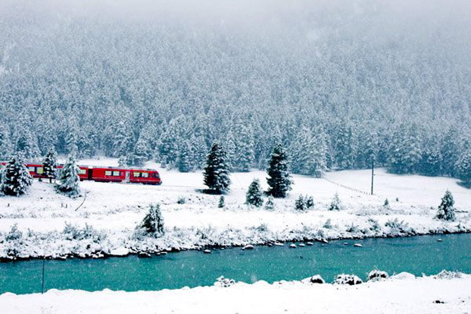 The Bernina Express, resplendent in its red livery, snakes through a snowy, Swiss landscape.
