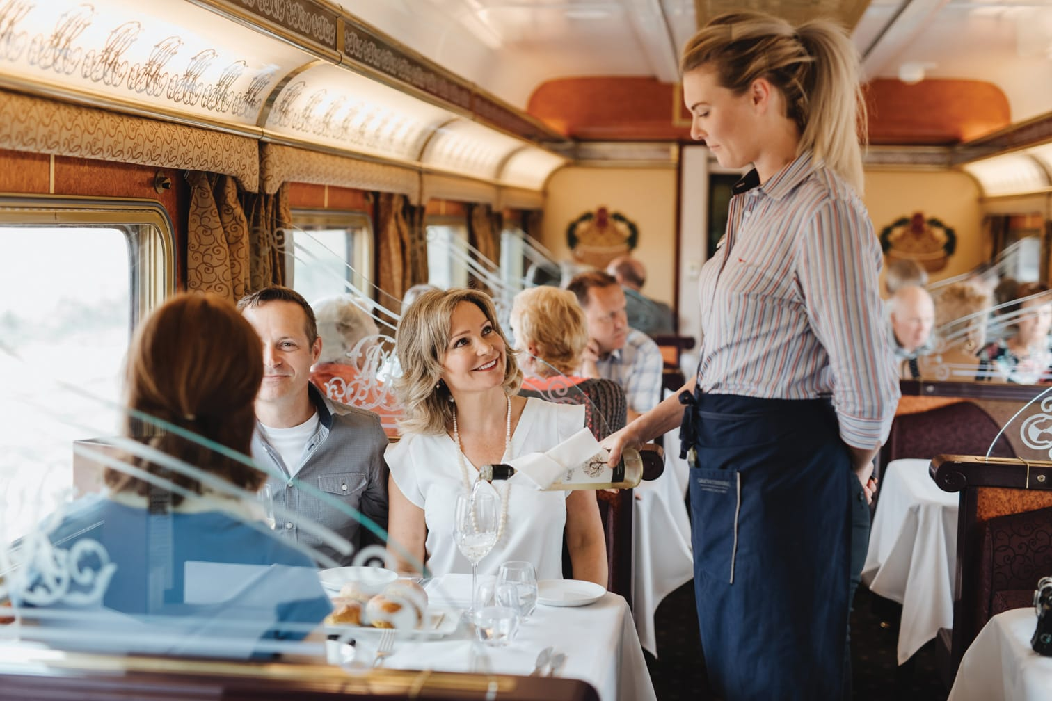 Server on the Ghan train pouring wine