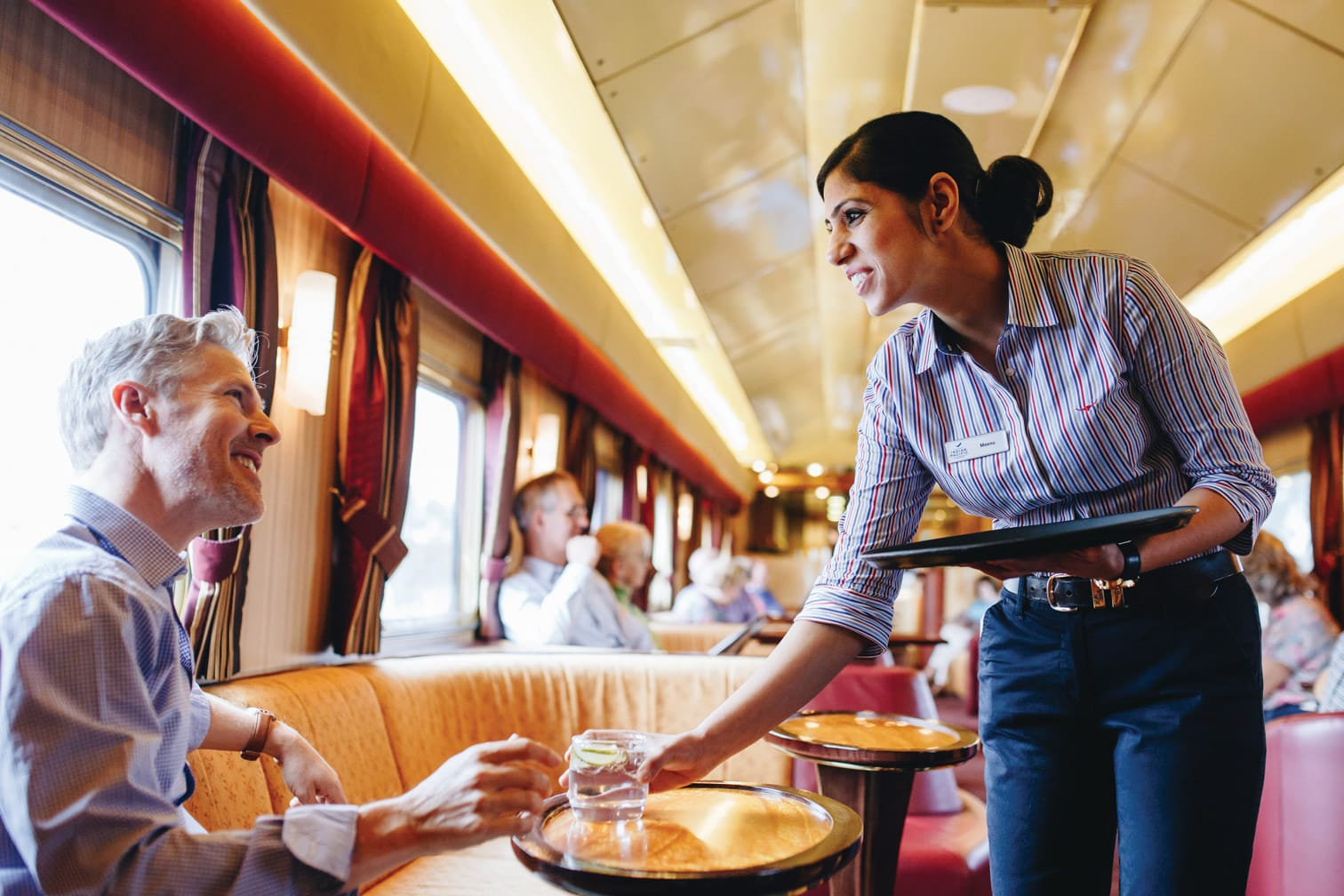 Serving a drink to a guest on the Indian Pacific train