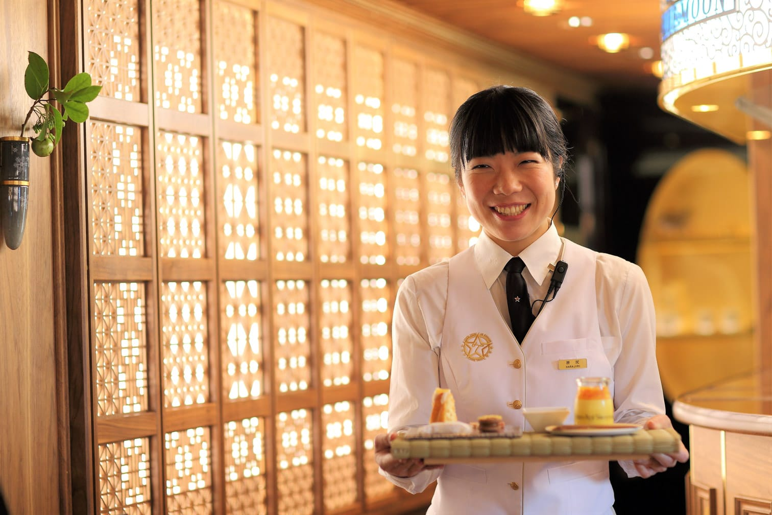 Service staff holding food on the Kyushu Seven Stars train