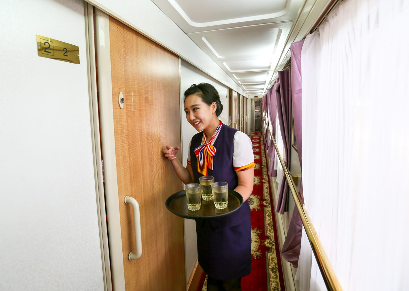 Train attendant providing service to a cabin on the Shangri-La Express train