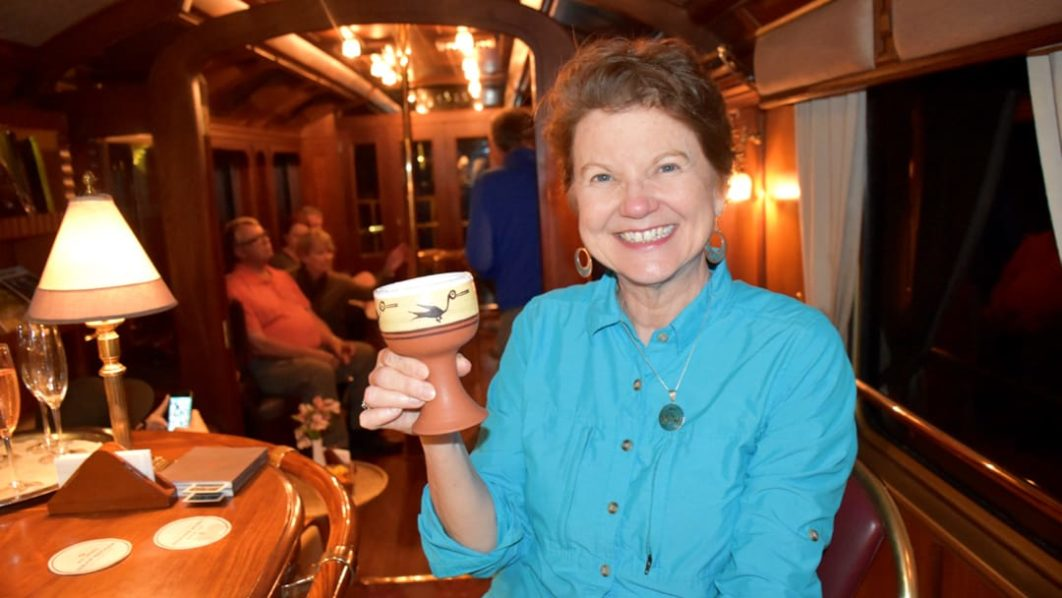Female guest holding a drink on the Belmond Hiram Bingham train