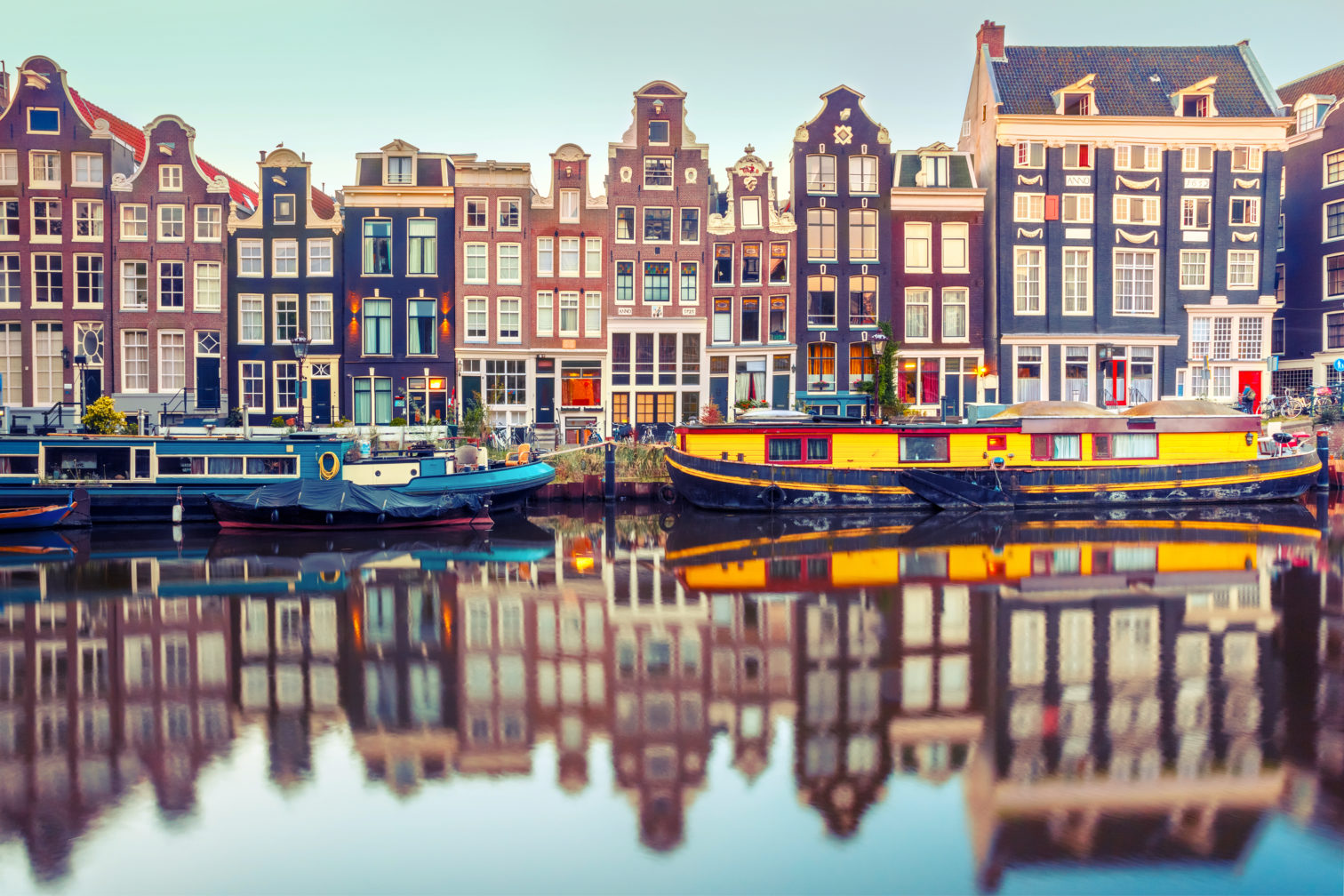 Canal in Amsterdam with colorful boats.